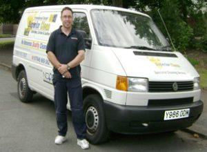 Peter standing by company van