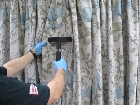 A curtain being professioanl dry cleaned using safe solvents